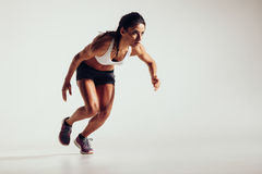Young woman starting to run and accelerating. Over grey background. Powerful young female athlete running in competition Stock Photo