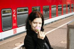 Young woman at the station. Young woman sitting at the station smiling with a rose stock photos