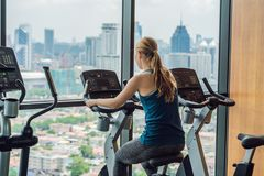 Young woman on a stationary bike in a gym on a big city backgrou. Nd Stock Image
