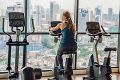 Young woman on a stationary bike in a gym on a big city background.  Stock Photos