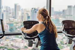 Young woman on a stationary bike in a gym on a big city background.  Stock Images