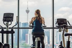 Young woman on a stationary bike in a gym on a big city background.  Stock Photo
