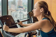 Young woman on a stationary bike in a gym on a big city background.  Stock Photography
