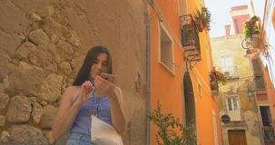 Young smiling woman stay in city at morning and using smartphone. Girl browse the Internet, texting with someone. Young woman stay in city at morning and using stock video footage