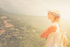 Young woman stay at edge of cliff looking over expansive view of plains and mountains.  stock photo