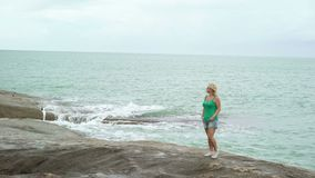 Young woman staying near sea. Young blonde woman staying near sea and raising hands up stock video footage