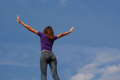 Young woman staying with raised hands. Against blue sky Royalty Free Stock Image