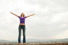 Young woman staying with raised hands. Against blue sky Royalty Free Stock Photography