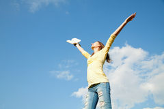 Young woman staying with raised hands. Against blue sky Stock Images