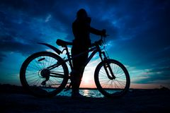 Young woman staying on the shore of the lake with bicycle at sun stock image