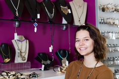 Young woman staying in the store. Portrait of cheerful young woman staying in the store of jewelry Royalty Free Stock Photo