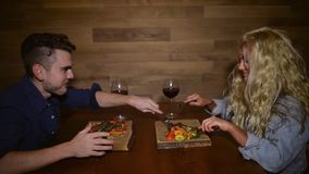 Young woman stealing food from boyfriend. Plate at table in evening on background of wooden wall. Cute couple eats dinner with red wine at home stock video