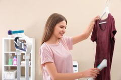 Young woman steaming her clothes. At home stock photo
