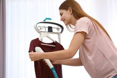 Young woman steaming her clothes on rack. At home royalty free stock photo
