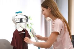Young woman steaming her clothes on rack. At home royalty free stock photos