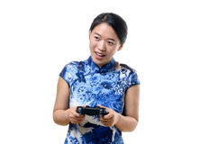Young woman steering with game controller. Excited single young woman in traditional dress with white dots steering with game controller over white background Stock Photography
