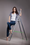 Young woman on step ladder. Stock Photos