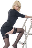 Young Woman Stepping on Ladder with Thigh Showing Wearing Black Stockings Stock Photo