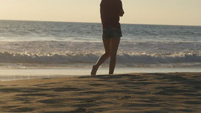 Young woman stepping at sand. Close up of female tourist walking on golden sand at the beach with ocean waves at stock video footage