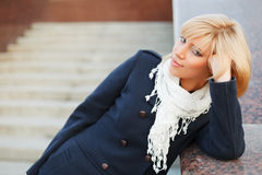 Happy young blond woman daydreaming. Happy young woman daydreaming on the steps Stock Image