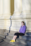 Young woman on steps in city. Young woman in athletic clothing listening to music on steps in city Stock Images