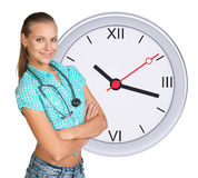 Young woman with stethoscope and clock Royalty Free Stock Image