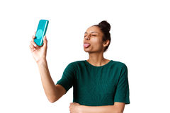 Young woman sticking out her tongue and taking selfie Stock Photo