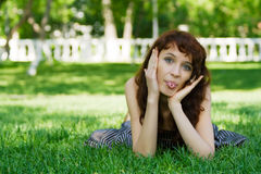 Young woman sticking out tongue. Young woman sticking out her tongue in the park royalty free stock photography