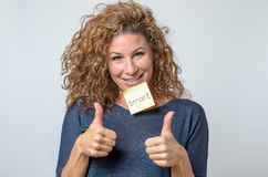 Young woman with a sticky note in her face Stock Photo