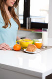 Young woman still life portrete. Young woman having breakfast at home, eating healthy food, fruits, milk, cereals and orange juice Royalty Free Stock Image