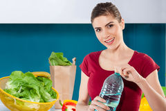 Young woman still life portrete. Portrait of a Smiling woman in kitchen holding a bottle of water Royalty Free Stock Images