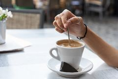 Young woman stirring a coffee stock photography