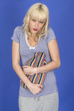 Young Woman with Stomach Ache Holding a Hot Water Bottle Stock Photos