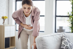 Young woman with stomach pain Royalty Free Stock Photos