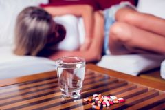 Young woman with stomach pain lying on the sofa. Medicine and he stock image