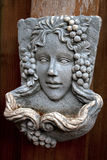 Young woman stone mask with decoration of grapes Stock Photo