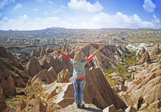 Young woman  on a stone   with raised hands. On the  top of   mount  against the background of incredible landscape with  mountains , geological structures in Royalty Free Stock Photo
