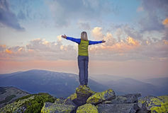Young woman  on a stone   with raised hands. On the  top of   mount Great Sivulja  ,Carpathian ,Ukraine Stock Photos