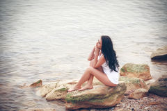 Young woman on stones near sea Royalty Free Stock Photos