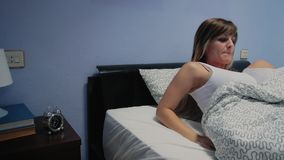 Young woman stopping alarm clock