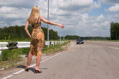 Young woman stopping the car. Young woman stopping car on highway Royalty Free Stock Photos