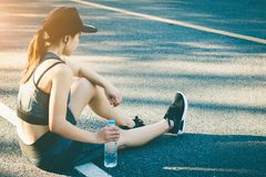 Women stops drink water resting after running. Young woman stops drink water resting after running Royalty Free Stock Photography