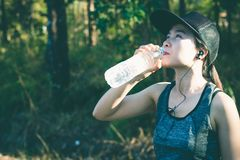 Women stops drink water resting after running. Young woman stops drink water resting after running Royalty Free Stock Photos