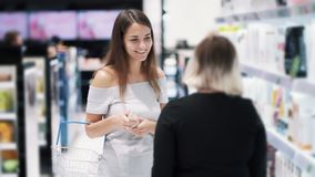 Young woman in store chooses shampoo, seller consultant talks about cosmetics, slow motion. Concept of shopping center, purchases stock video footage