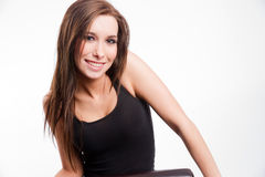 Young woman straddling common chair looking happy Stock Photography