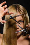 Young woman with straight hair and scissors Stock Image