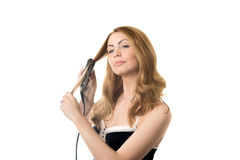 Young woman straightening curly hair Stock Images