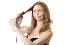 Young woman straightening frizzy hair. Funny frowning young attractive blond woman holding hair straightener, in bad mood because of her hairstyle, studio royalty free stock image