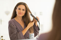 Young woman straightening hair in bathroom Royalty Free Stock Photography