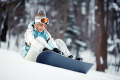 Young woman strapping on Snowboard Stock Image